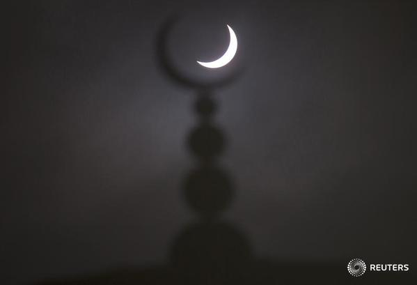 Eclipse2015 is seen above a mosque in Oxford, England